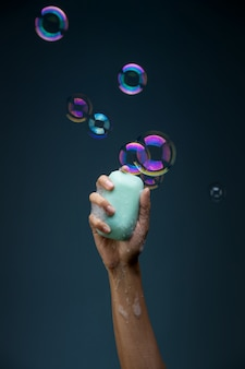 Hand holding soap bar and bubbles, victory against coronavirus concept