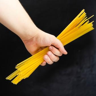 Hand holding spaghetti