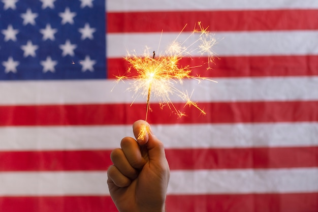 アメリカの国旗の前で線香花火を持っている手