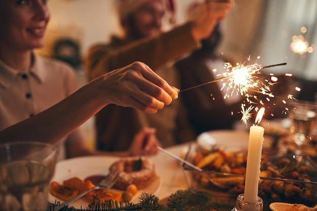 Hand holding sparkler over table