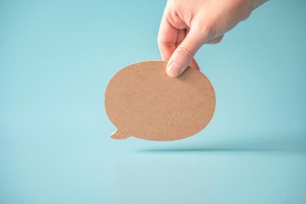 Hand holding speech bubble.