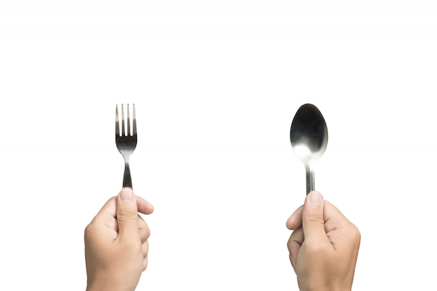Hand holding spoon and fork on isolated background.
