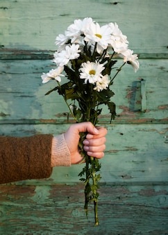 Hand holding spring flowers bouquet