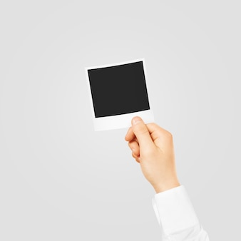 Hand holding square blank photo mockup.