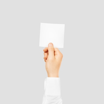 Hand holding square blank white card isolated