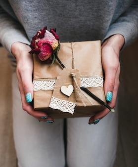 Mano che tiene pacchetto marrone piazza con un fiore