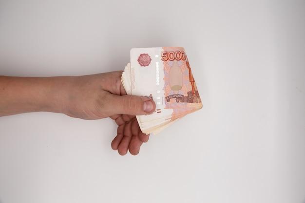 Рука стека российских рублей.