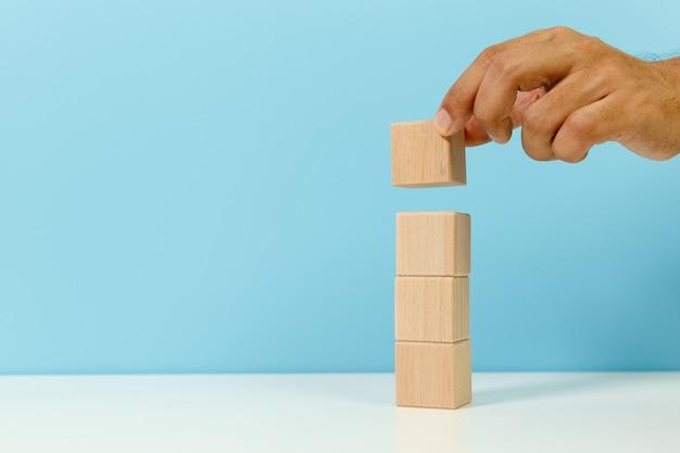 손을 잡고 쌓인 빈 나무 큐브 블록 파란색 배경. 관리 및 선택 개념입니다.