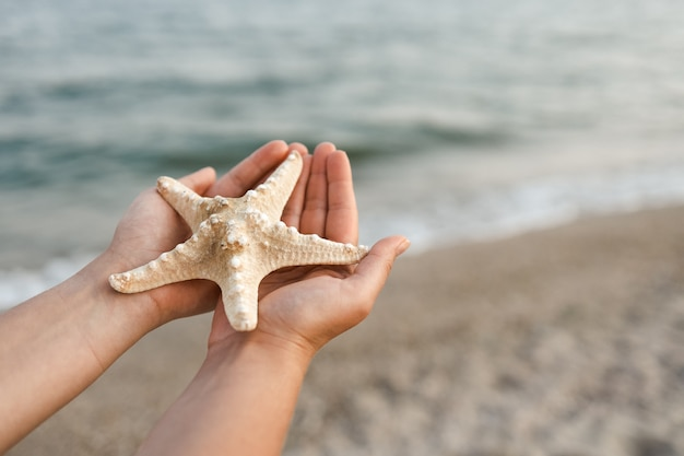Hand holding starfish with beautiful tropical summer sand beach island, relaxing vacation summer blue sea concept.