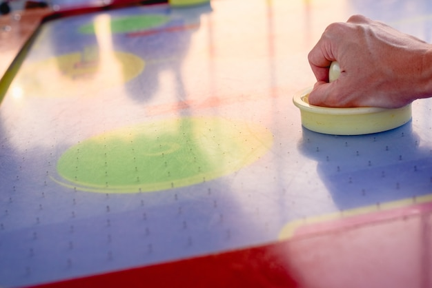 Hand holding a stick to hit disc in the table air hockey game.