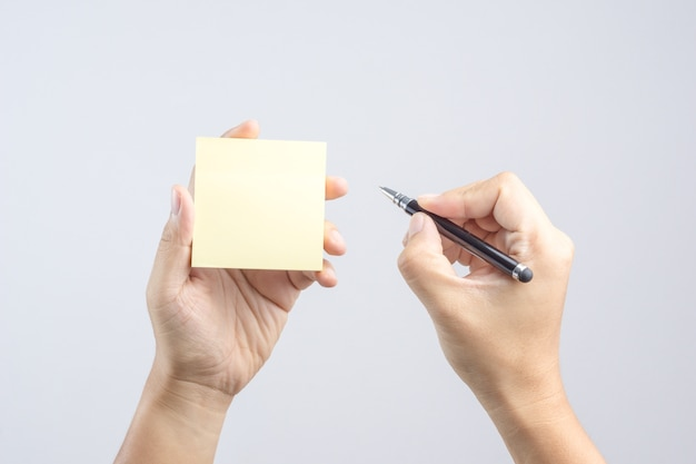Hand holding sticky post note paper sheet