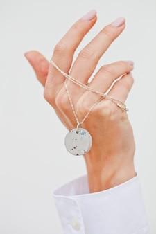 Hand holding stylish necklace.