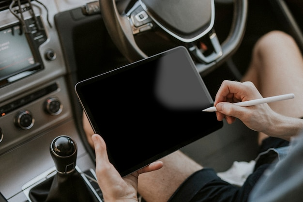 Hand holding stylus pen on a tablet screen in a car