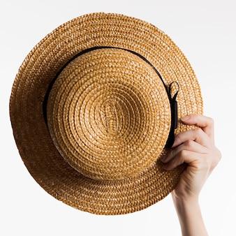 Рука держит шляпу от солнца