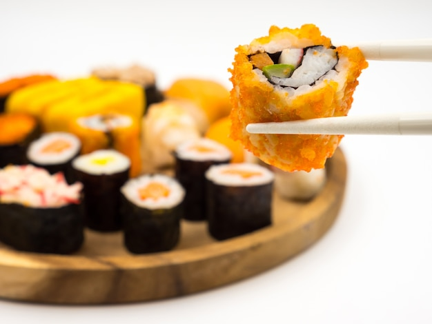 Hand holding sushi roll with chopsticks, sushi set on wooden plate background, japanese food.