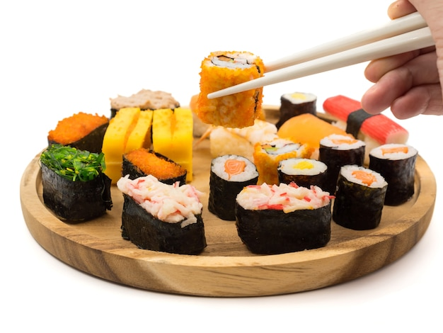 Hand holding sushi roll with chopsticks,