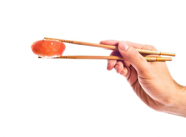 寿司を箸で手に持って