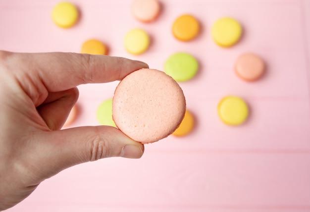 甘くてカラフルなフランスのマカロンやピンクのテーブルにマカロンを持っている手