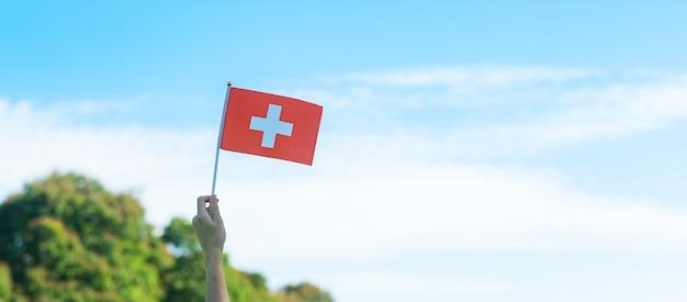 青空の背景にスイスの旗を持っている手。スイス建国記念日と幸せなお祝いの概念