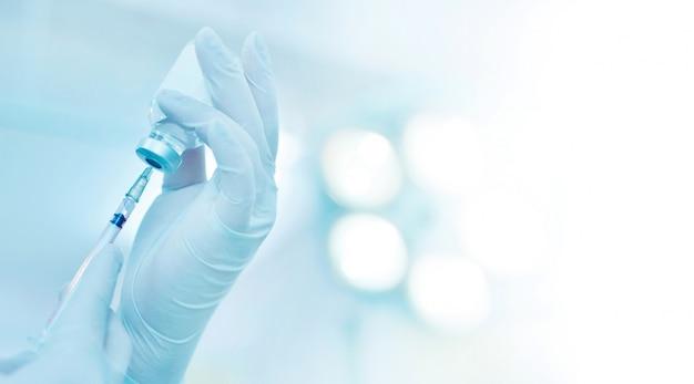 Рука шприц и флакон с лекарством готовятся к инъекции в операционной с хирургическим фоном лампы
