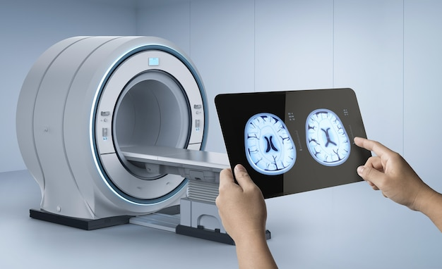 Hand holding tablet display xray brain with mri scan machine