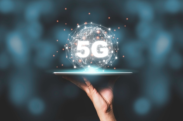 Hand holding tablet with 5g  and virtual global connection line. communication technology transformation concept.