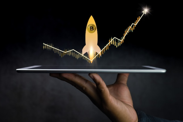 Hand holding a tablet with design of a graph and a rocket coming out of it on dark background