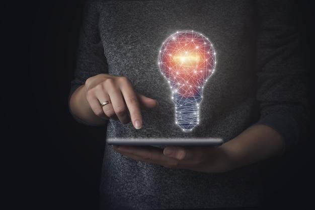 描画電球付きの手持ちタブレット。革新とインスピレーションでクローズアップ、アイデアのコンセプト。