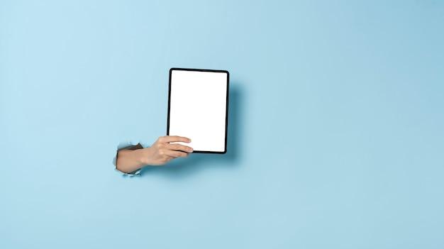 テキストスペース青い背景を持つタブレットを持っている手。
