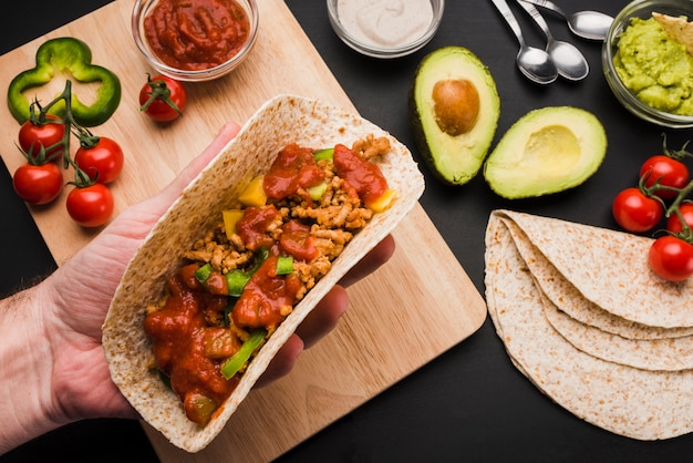 Hand holding taco near cutting board among vegetables and sauces