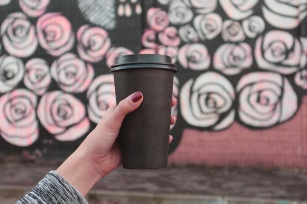 手を持って離れて黒のコーヒーカップを取る