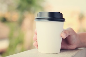 Hand holding take away coffee cup with retro filter effect