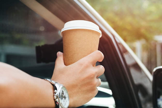 Hand holding takeaway coffee in a car