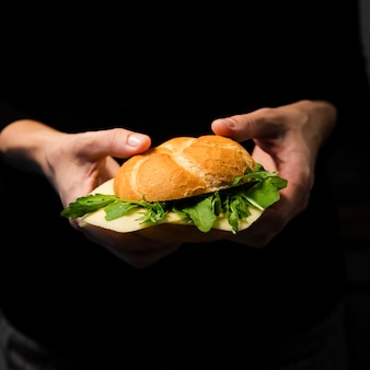 Hand holding tasty bagel with lettuce