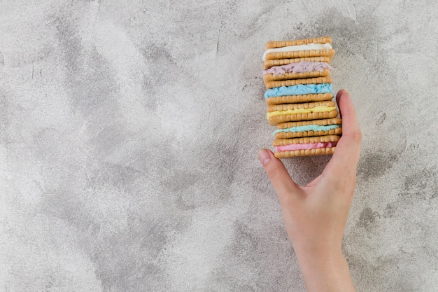 Hand holding tasty cookies on grey background