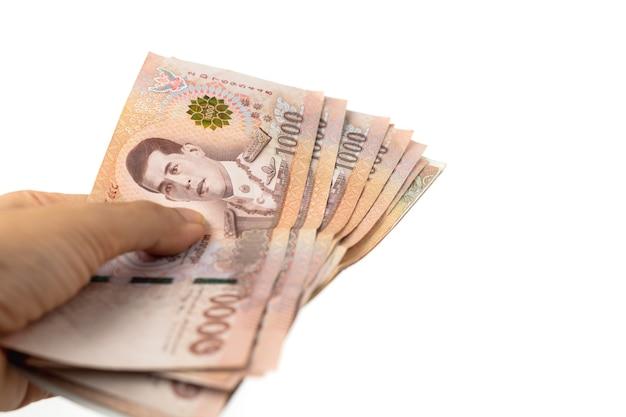 手持ちのタイ通貨、1000バーツ、ビジネスと金融の概念のための白い壁にタイのお金の銀行券
