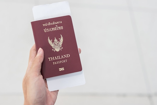 Hand holding thailand passport and boarding pass ticket.