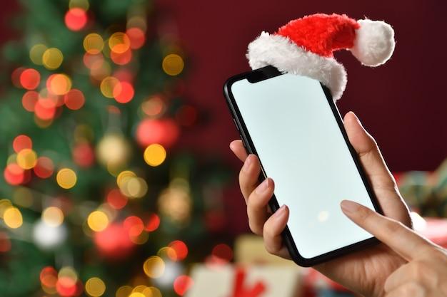 空白の画面とクリスマスの背景の上にサンタクロースの帽子と黒いスマートフォンを持っている手