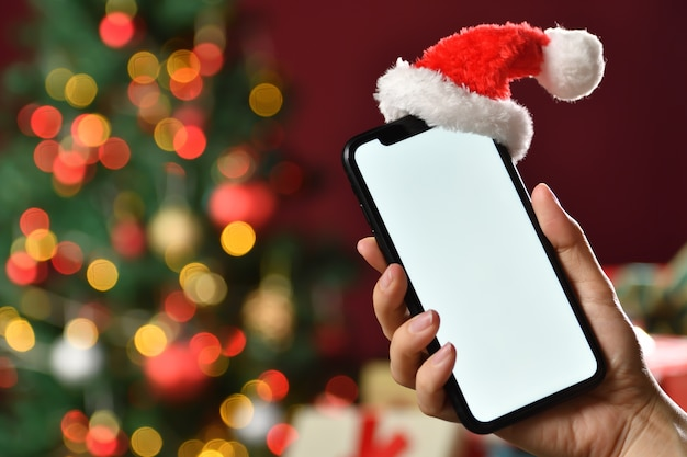 空白の画面とサンタクロースの帽子が上にある黒いスマートフォンを持っている手