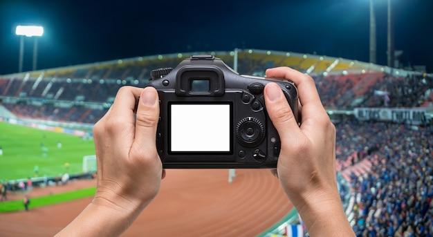 경기장에 관중의 추상 흐리게 사진 군중을 통해 카메라를 들고 손