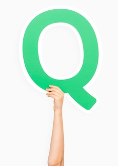Hand holding the letter Q