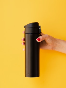 Hand holding thermos mock-up on yellow background