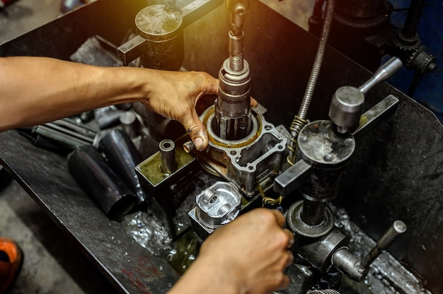 Рука, крепко держащая цилиндр на хонинговальном станке для мотоцикла