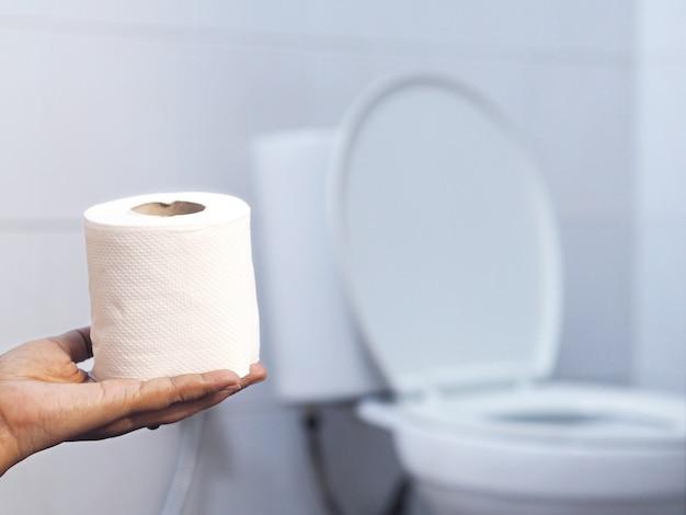Hand holding tissue over blurry white toilet