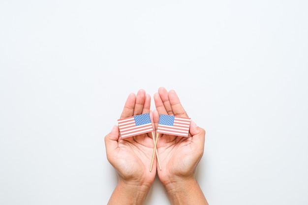 Hand holding and touching national mini american flag. world veteran day concept