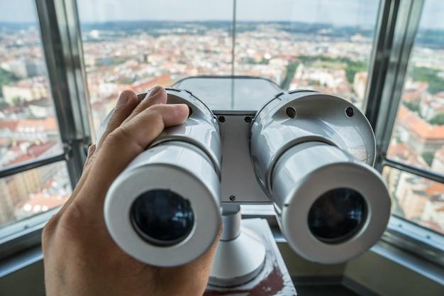Рука туристический бинокль и размытый город на фоне в высокой точке зрения. прага