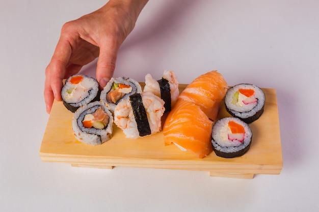白い背景で隔離の伝統的な日本の新鮮な巻き寿司を持っている手。