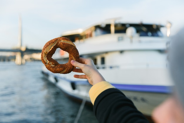 Hand holding traditional turkish bagel simit the blue bosphorus bay background.