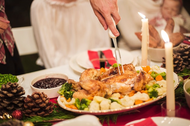 Hand holding turkey with fork at christmas table