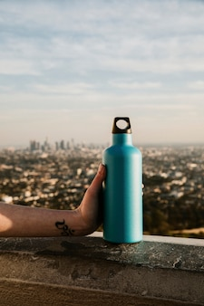 Hand holding a turquoise stainless steel bottle with urban view